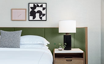 guestroom bed with nightstand and lamp